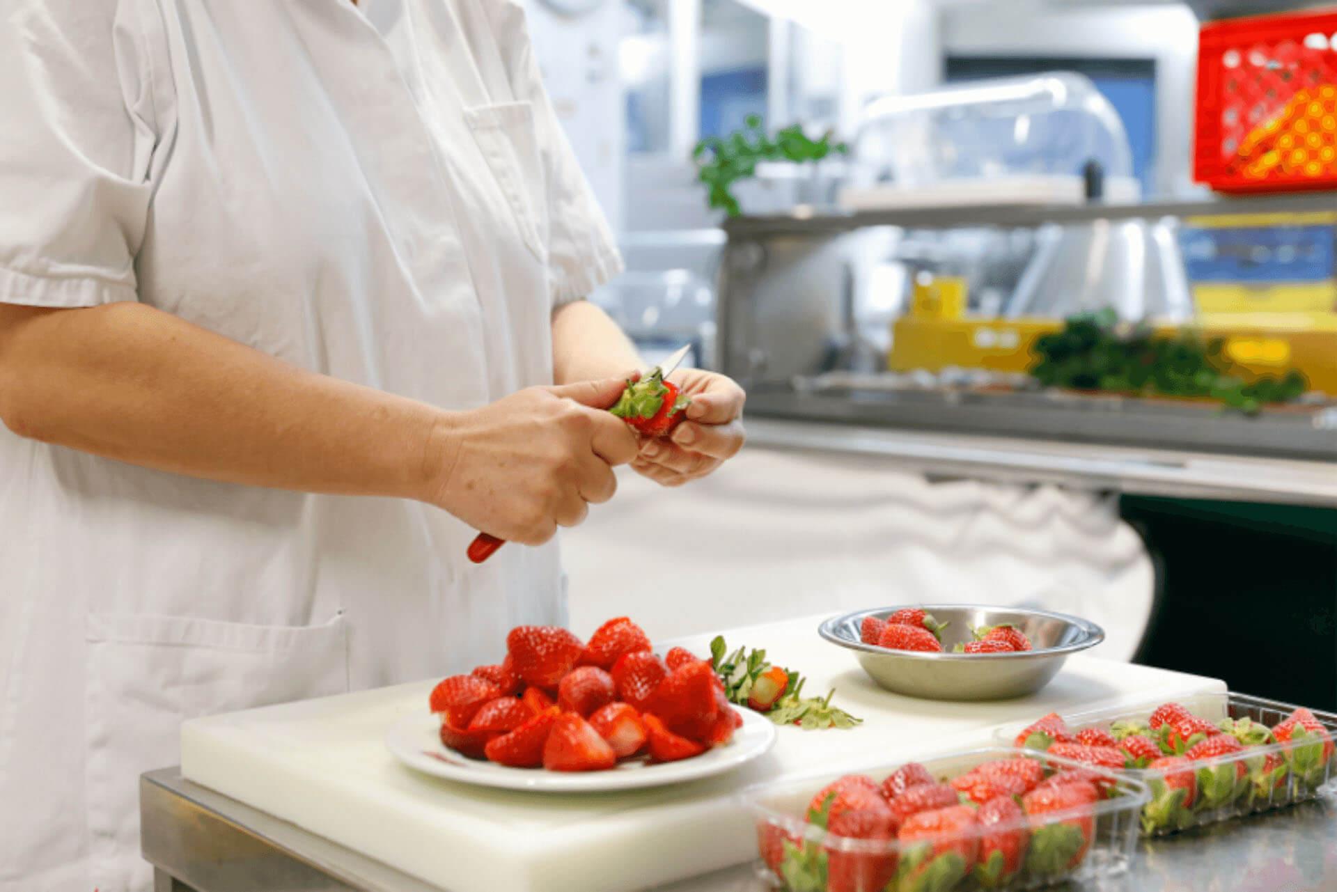 Eine Mitarbeiterin beim Schneiden von Erdbeeren in der Küche