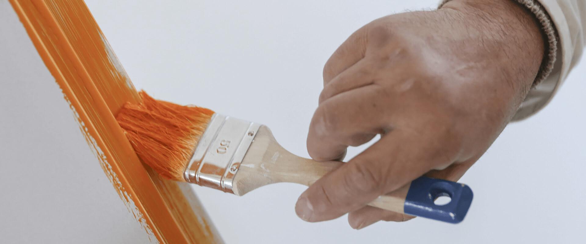 Mitarbeiter beim Streichen eines Tührrahmens