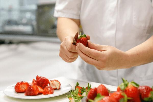 Mitarbeiter beim Schneiden von Erdbeeren